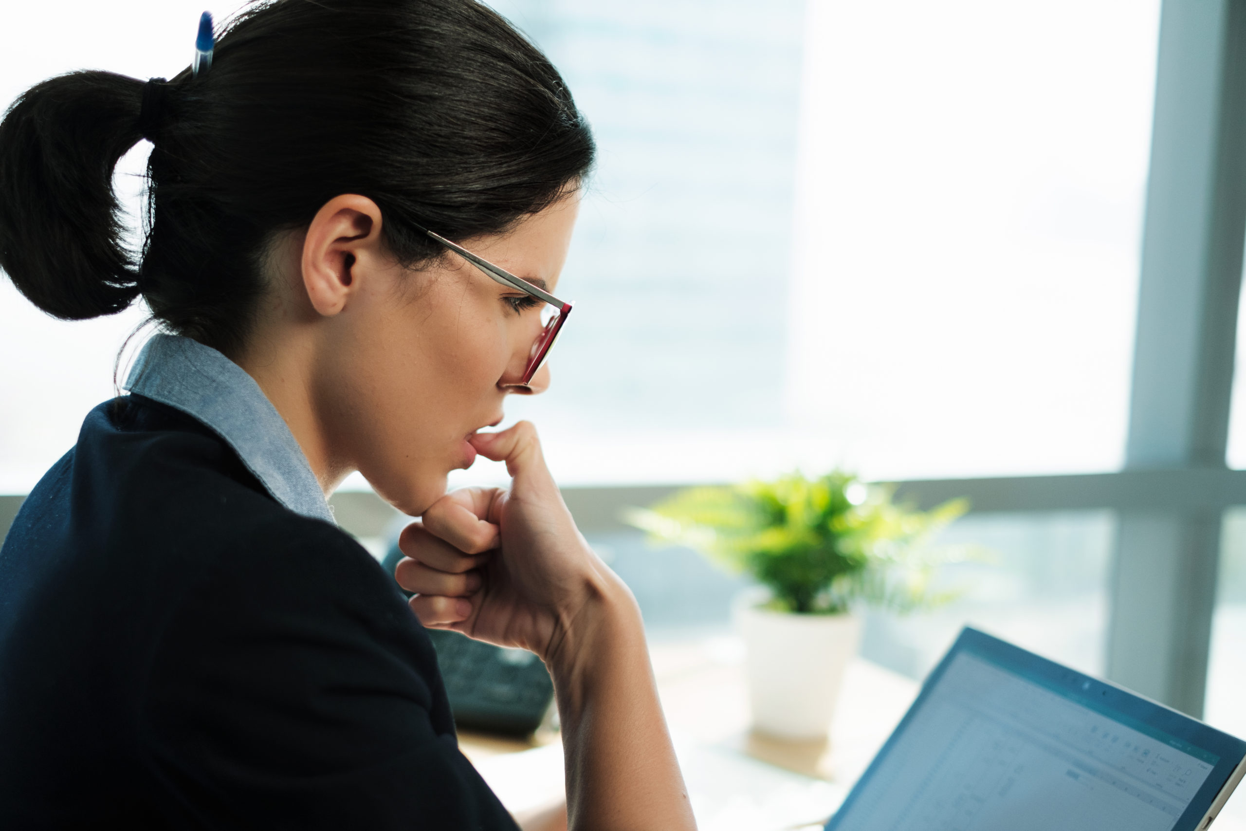 Bored business woman biting her nails at work while looking at a computer screen. Young nervous female executive worker with bad habits chewing on her fingernails while at the workplace. Side View