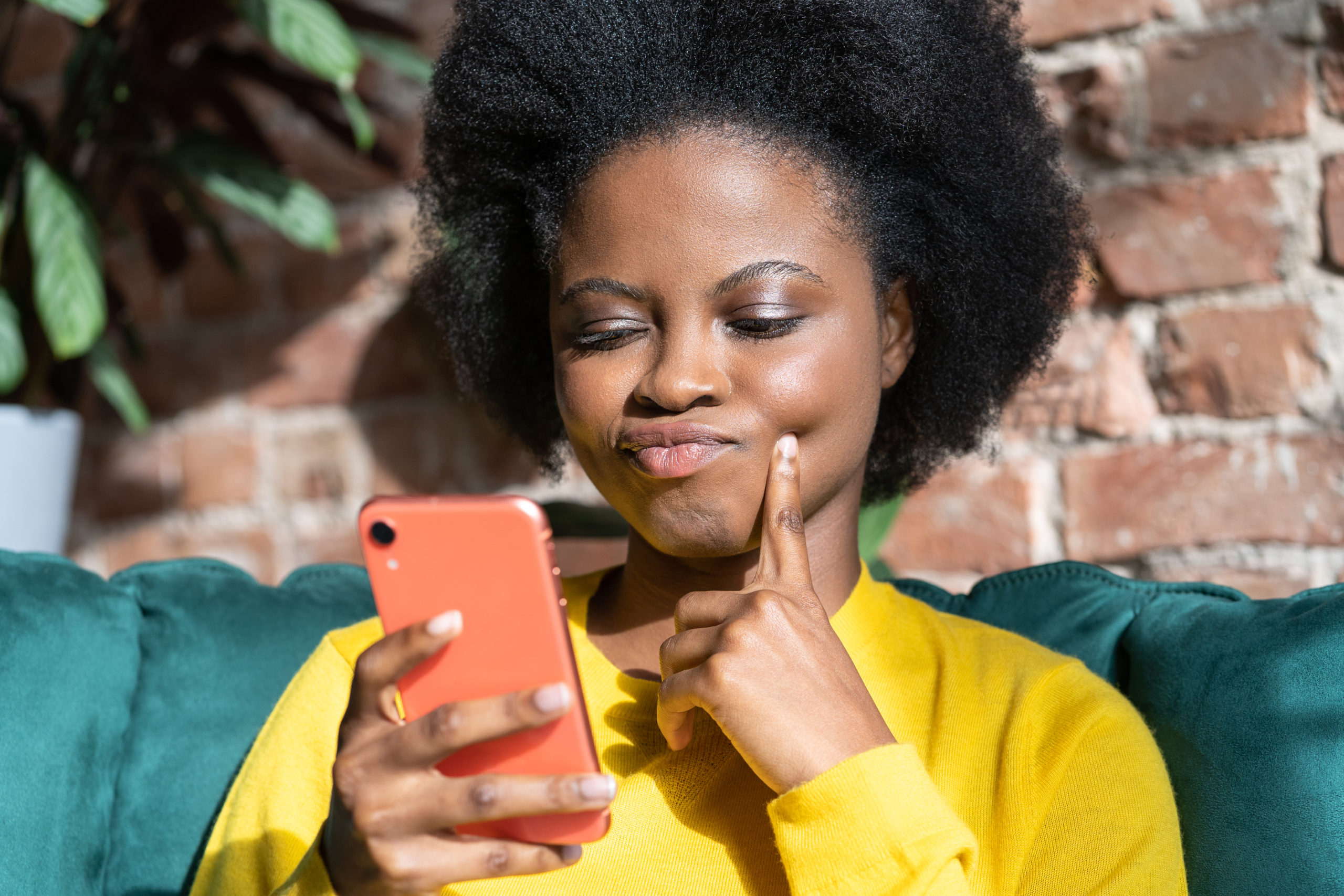 Afro-American woman ponders on how to answer question, thinks deeply about something, using mobile phone, tries to made up good message, keeps index finger on cheek, sitting on armchair, indoors.