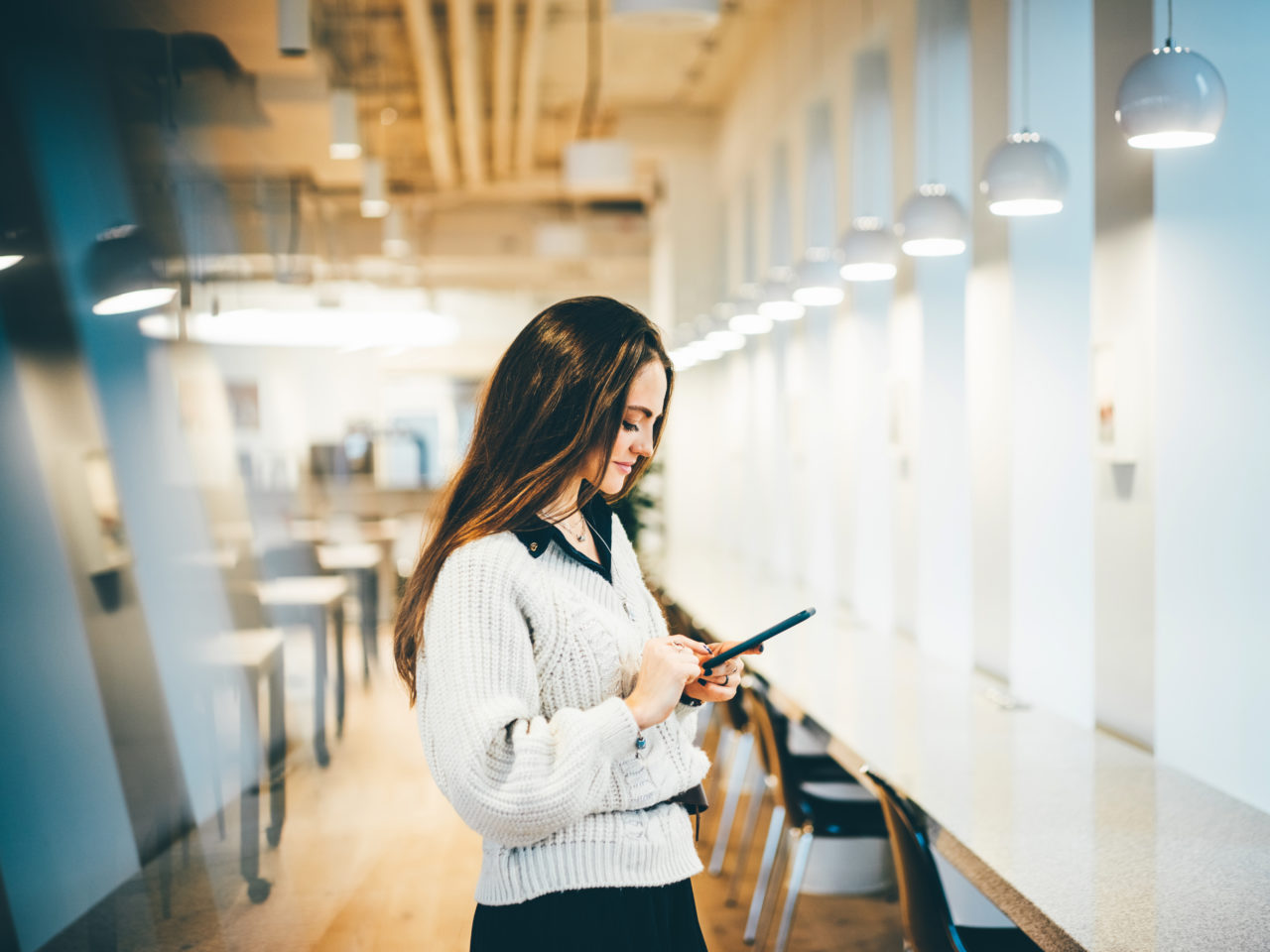 Elegant woman using mobile phone in modern office , businesswoman read text message on telephone. Businesswoman texting email letter on phone using internet.