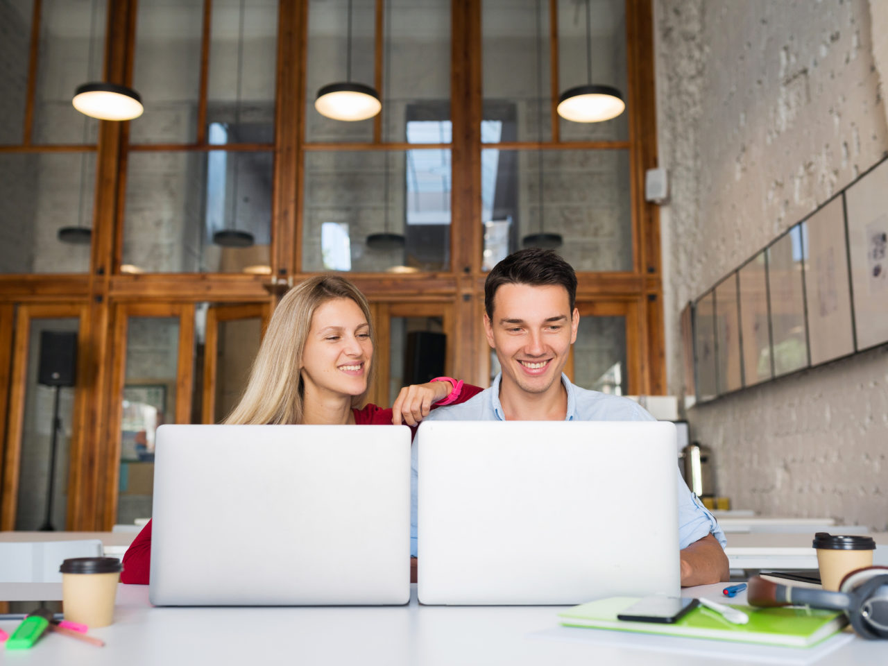 modern young man and woman working on laptop in open space co-working office room, freelancers, cooperation, startup, creative job